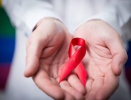 @Glowimages: Man in shirt holding red aids ribbon on rainbow background